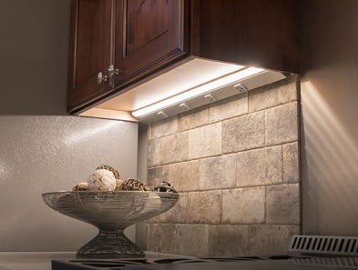 A Task Lighting lighted power strip hidden underneath a mounted wall cabinet.